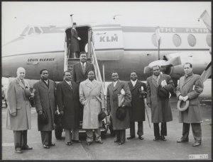 Op Schiphol arriveerde een goodwill-delegatie uit Ghana (o.l.v. De minister van Handel, P.K.K. Quaidoo, midden in lichte jas met bril) die een bezoek van enkele dagen aan ons land zal brengen. Uiterst links dr. E. van Konijnenburg, onderdirecteur van de KLM en uiterst rechts mr. H.I. Borel Rinkes, plv. hoofd dienst buitenlandse samenwerking KLM.